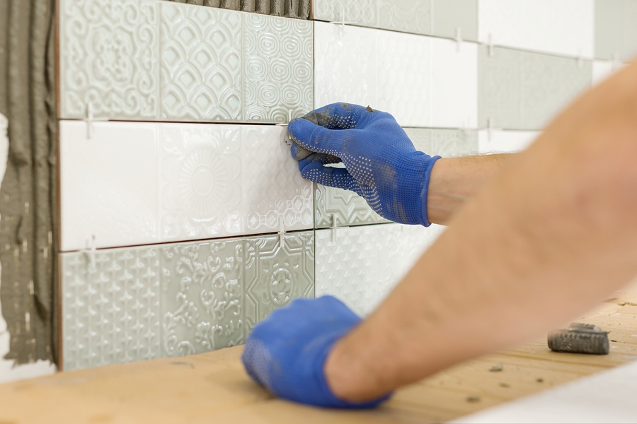 worker gluing tiles on to walls