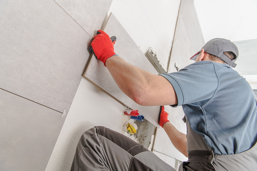 worker installing tiles on walls